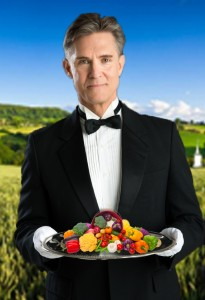 Confident Waiter Holding Serving Tray Against Black Background